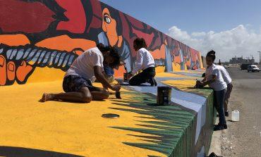 Artistas locales restauran el mural Reflejos
